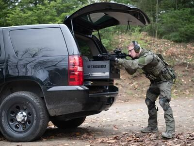 A man Shooting a gun that is resting on a TruckVault in the back of a black Chevy Tahoe.