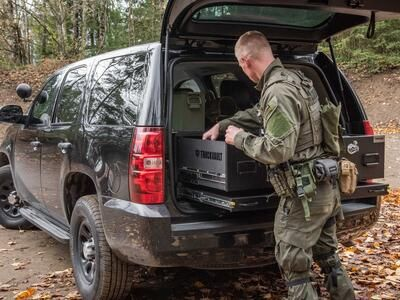 A man wearing tactical clothing grabbing equipment out of a TruckVault inside of a black Chevy Tahoe.