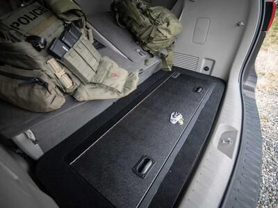 A Kia Sedona FloorVault next to two police backpacks.