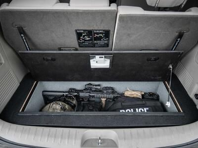 An open Kia Sedona FloorVault filled with a gun and other police gear.