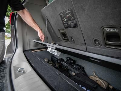 A man opening a Kia Sedona FloorVault filled with a gun and other police gear.