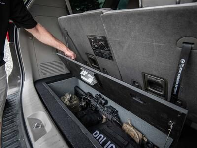 A policeman opening a Kia Sedona FloorVault with a gun and police equipment in it.
