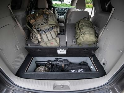 A Kia Sedona FloorVault filled with a gun and police gear. Next to two police backpacks.