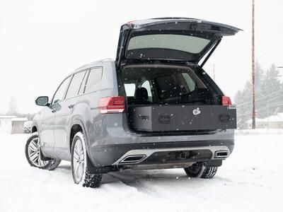 A Volkswagen Atlas parked in the snow with an open TruckVault in the rear.