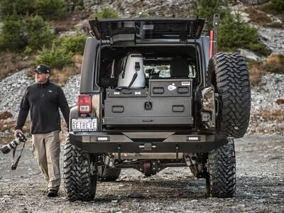 A man with a camera walking next to a 2013 Jeep Wranger with a TruckVault in the cargo space.