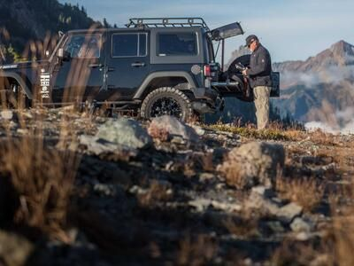 A man changing out a camera lense behind a black 2013 Jeep Wrangler with a TruckVault and a heavy duty pull out table in the mountains.