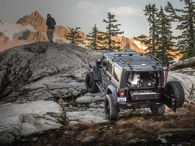 A gray Jeep Wrangler with a custom TruckVault parked on rocks in a mountain range with a man overlooking a valley.