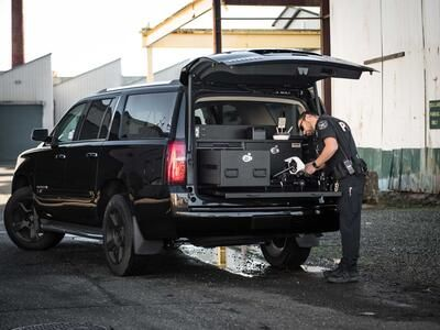 A police officer working on his drone on a pull-out table attached to his black Chevy Suburban.
