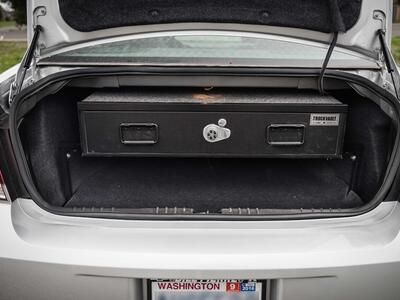 A silver Chevy Impala with an Elevated TruckVault in the trunk space.