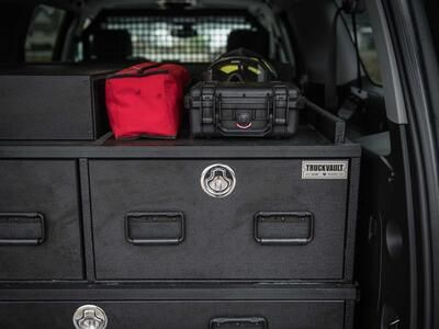 A custom TruckVault with boxes on top. All inside of a red Chevy Suburban.
