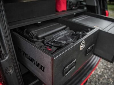 An up-close image of a custom, open TruckVault inside of a red Chevy Suburban.